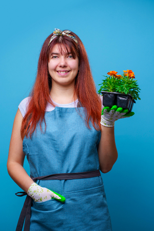 Photo of happy brunette girl with marigolds in her hands