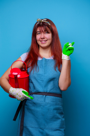 Photo of happy female florist with watering can in hands of pointing finger to side