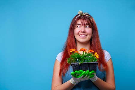 Photo of happy brunette at side with marigolds in her hands