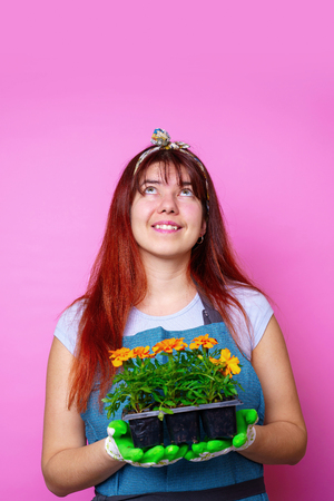 Photo of happy woman looking up with marigolds in her hands 스톡 콘텐츠