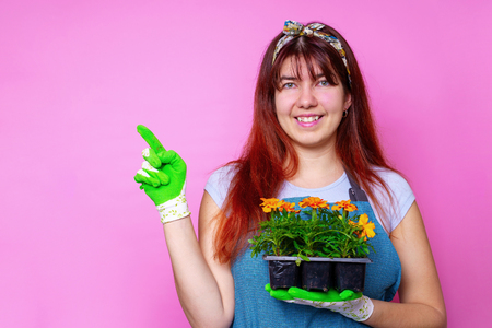 Image of happy woman with marigolds , pointing to side