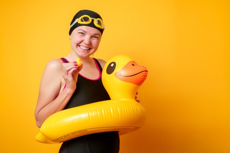 Image of happy woman in bathing suit with lifebuoy on empty orange background