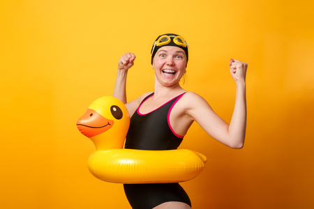 Photo of strong woman in swimsuit with life preserver on empty orange background Reklamní fotografie