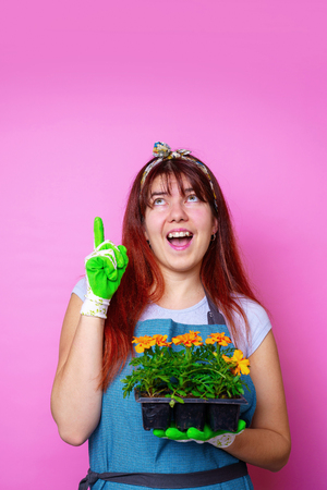 Image of happy woman looking up with marigolds in her hands