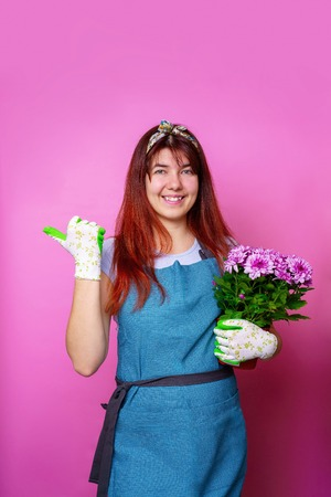 Photo of cheerful girl with chrysanthemum pointing hand to side