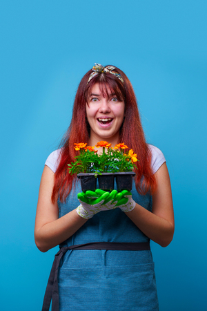 Image of happy brunette with marigolds in her hands