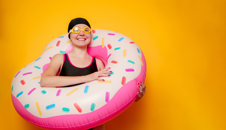 Photo of happy girl in swimming goggles, swimsuit with donut life buoy on empty orange background Stock Photo