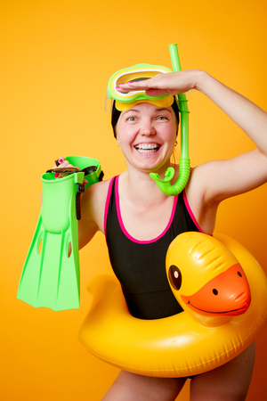 Photo of happy woman with flippers in hands, swimming mask and with life preserver on empty orange background Reklamní fotografie