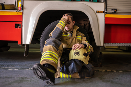 Photo of young tired fireman sitting on floor near fire truck