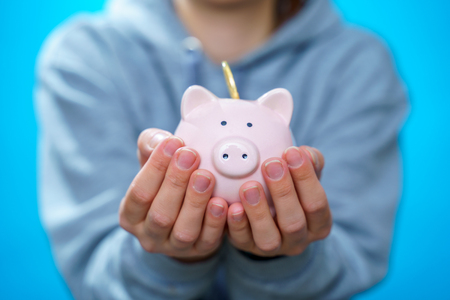Picture of man throwing coin into piggy bank on blue empty background