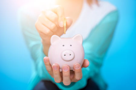 Image of woman throwing coin into piggy bank on blue empty background Фото со стока