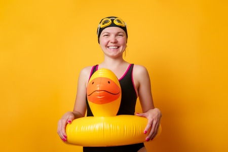 Image of smiling girl in bathing suit with lifebuoy on empty orange background