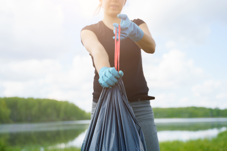 Image of woman in rubber gloves with full garbage bag on river bank