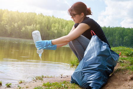 Photo of woman in rubber gloves with dirty plastic bottle in her hands on river bank
