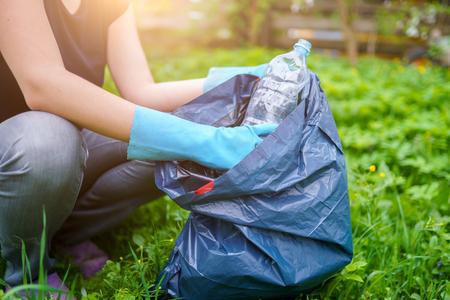Bild einer Frau in Gummihandschuhen, die eine schmutzige Plastikflasche auf dem Rasen aufhebt