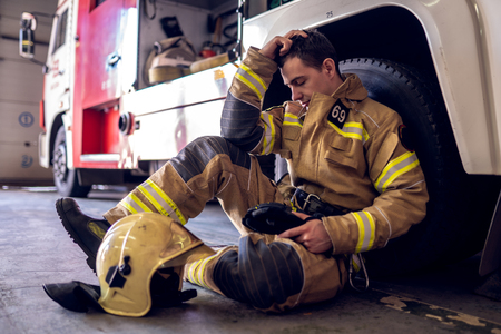 Photo of tired fireman sitting on floor near fire truck Banque d'images - 123692520