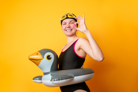 Picture of smiling girl in bathing suit with lifebuoy on empty orange background Stock Photo