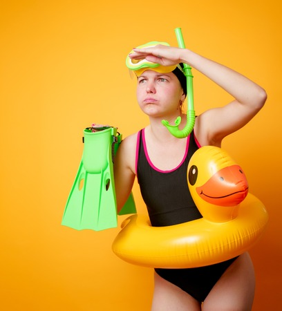 Photo of woman with flippers in hands, swimming mask and with life preserver on empty orange background