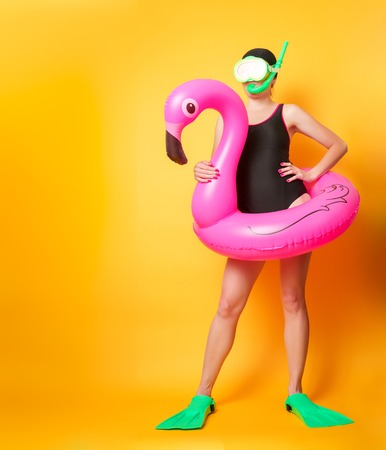 Full-length photo of girl in swimsuit with lifebuoy and flippers on empty orange background