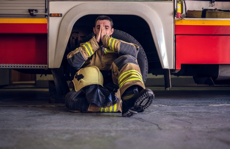 Image of tired fireman sitting on floor near red fire truck