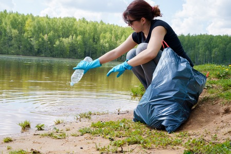 Image of woman in rubber gloves with dirty plastic bottle in her hands on river bank