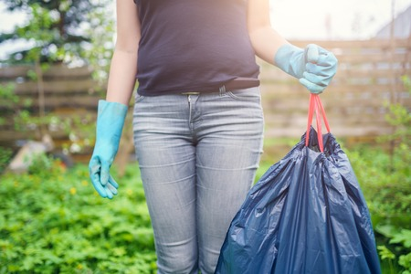 Photo of woman in rubber gloves with full garbage bag on garden Standard-Bild
