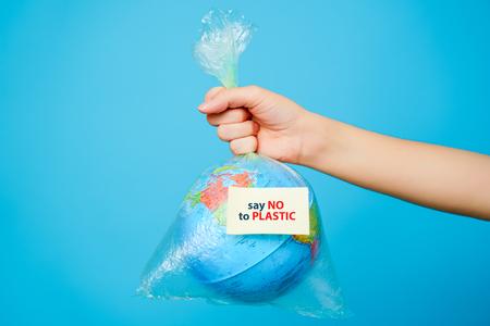 La donna tiene in mano un sacchetto di plastica e il pianeta terra con un adesivo di testo: Dì NO ALLA PLASTICA su sfondo blu Il concetto di inquinamento da plastica. Archivio Fotografico