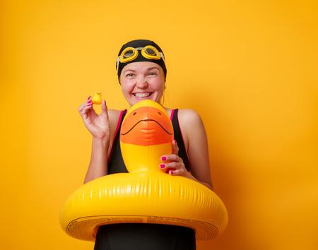 Image of smiling woman in bathing suit with lifebuoy on empty orange background