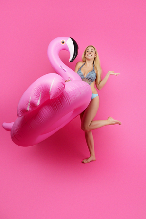 Full-length photo of blonde in bathing suit and pink glasses with pink inflatable flamingo on empty pink background
