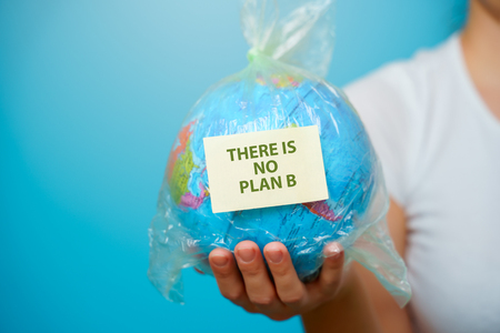 Woman holds in hands plastic bag with sticker text THERE IS NO PLAN B and planet earth at blue background. The concept of plastic pollution.