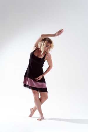 Photo of long-haired blonde in black dress looking down dancing in studio