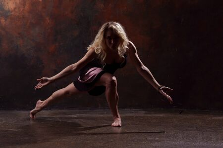 Full-length photo of dancing blonde girl in black dress on brown background