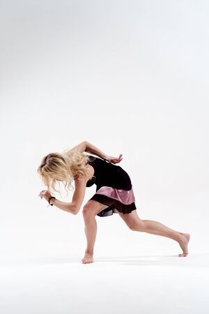 Photo of side of long-haired blonde with stretched hand dancing in studio