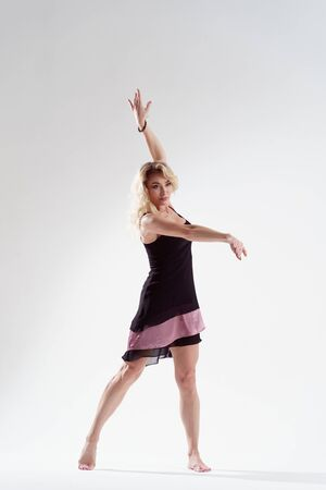 Photo of long-haired blonde looking to side with raised arms dancing in empty studio