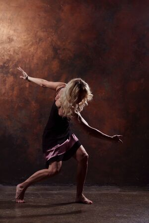 Full-length photo of young dancer in short black dress on brown background Stock Photo