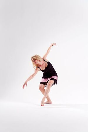 Photo of dancing blonde looking to side with raised arms in studio