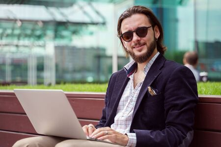 Photo of young brunet businessman with laptop sitting on wooden bench in city center on summer day