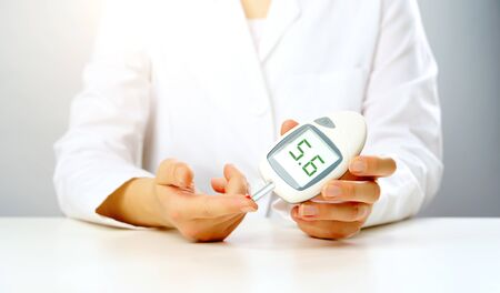 Photo of doctors hand with glucometer with inscription five in studio