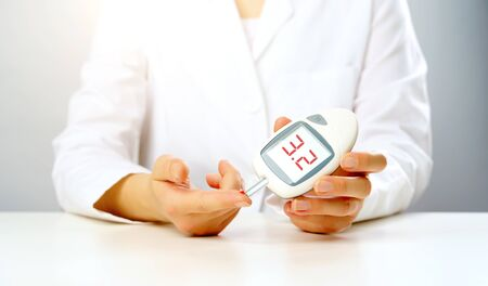 Photo of doctors hand with a glucometer with inscription three in studio on gray background