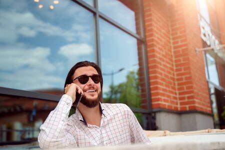 Foto van een jonge man die op de zomermiddag in een straatcafé in de stad aan de telefoon zit te praten