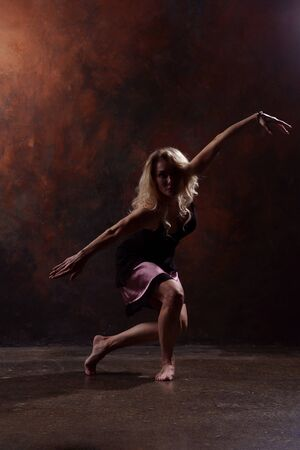 Photo of young dancing blonde woman in black dress on brown background