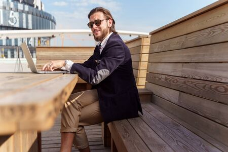 Photo on side of man in sunglasses sitting with laptop on wooden bench on spring
