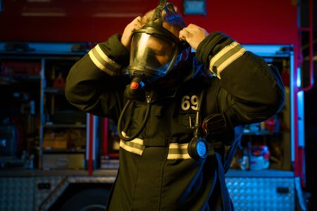 Photo of fireman putting on gas mask on background of fire engine at fire station. Neon effect