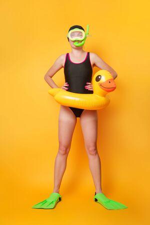 Zdjęcie pływaczki w czarnym stroju kąpielowym w płetwach z kołem ratunkowym dziecka w postaci kaczątka na pomarańczowym tle Zdjęcie Seryjne