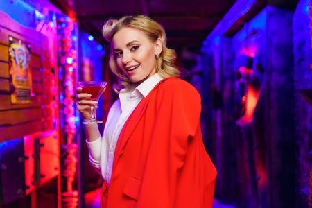 Photo of blonde woman with cocktail in her hand on red and blue background