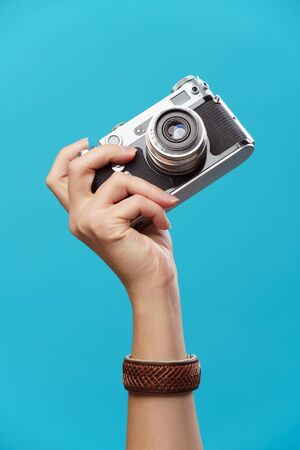 Picture of hand with phone on empty blue background in studio Banque d'images