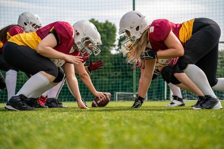 Photo of athletes wearing helmets playing american football on sports field Zdjęcie Seryjne