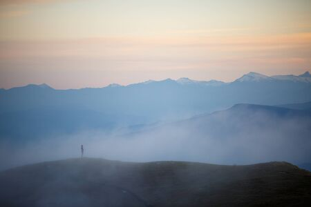 Photo of evening foggy mountain landscape with red sky