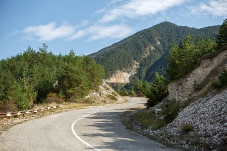Photo of picturesque mountain area, road, blue sky with clouds 스톡 콘텐츠