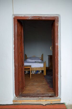 Photo of ancient building with open door, bed
